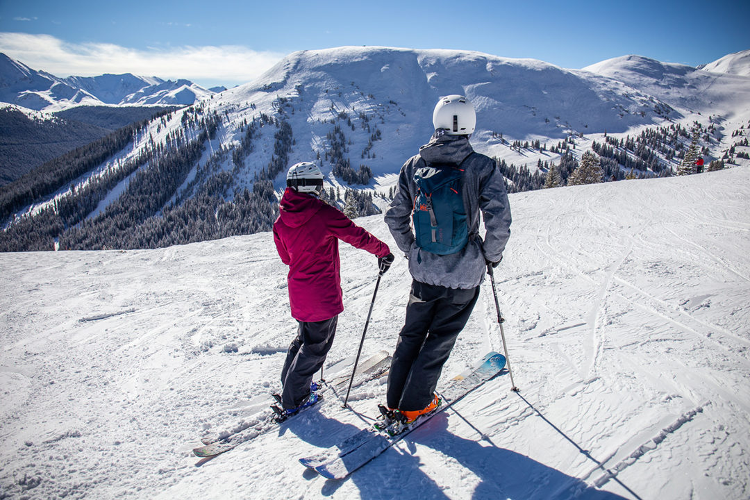 A female skier and male skier look across the ski slopes of Copper Bowl at Tucker Mountain, expert terrain located at Copper Mountain.