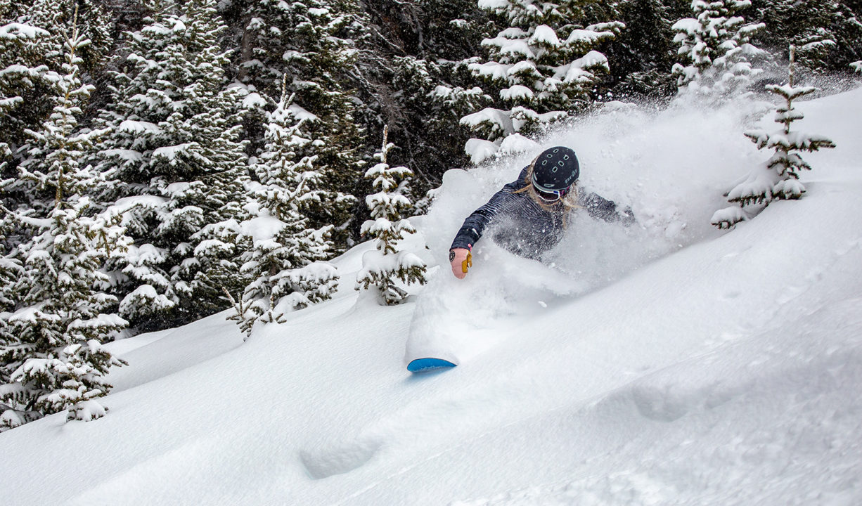 A female snowboarder rides through fresh powder at Copper Mountain.