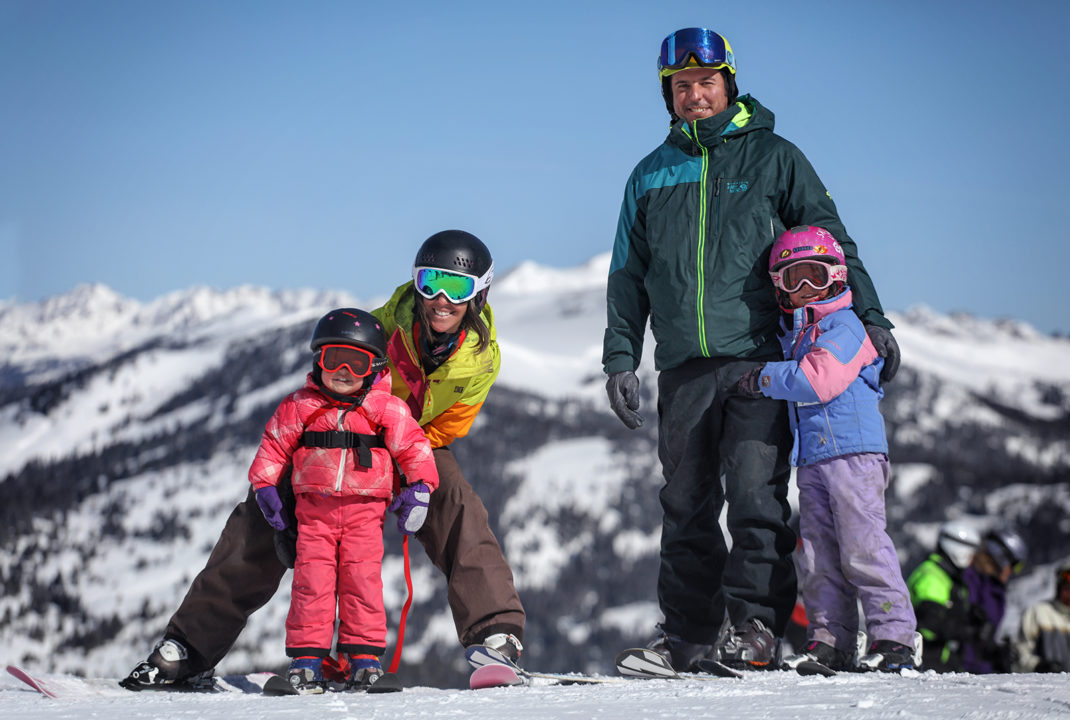 A family of four – a mother, a father, and two small children – smile for the camera as they stand in their ski gear at Copper Mountain.