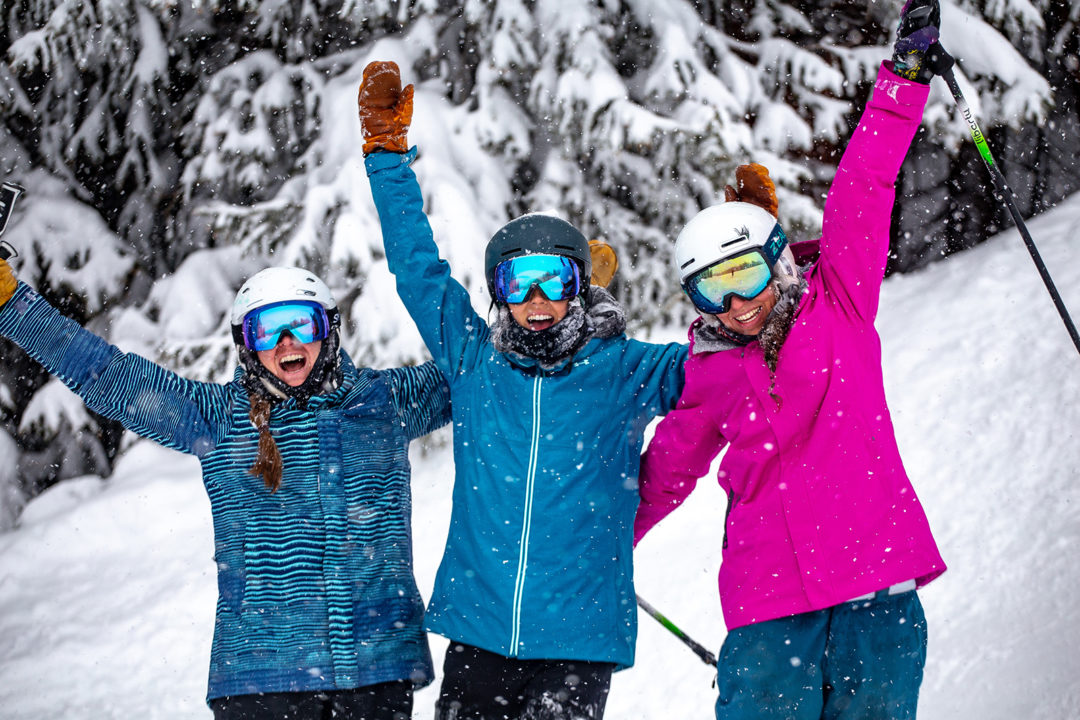 Three women smile for the camera while it snows at Copper Mountain.