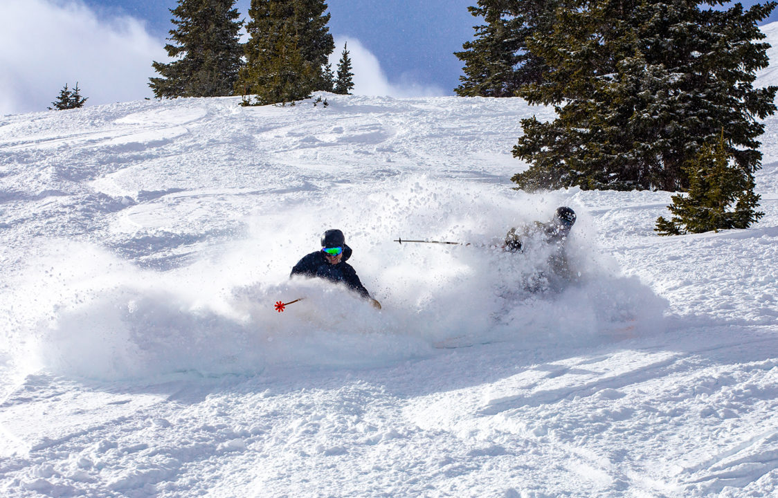 Two male skiers turn through deep snow at Copper Mountain.