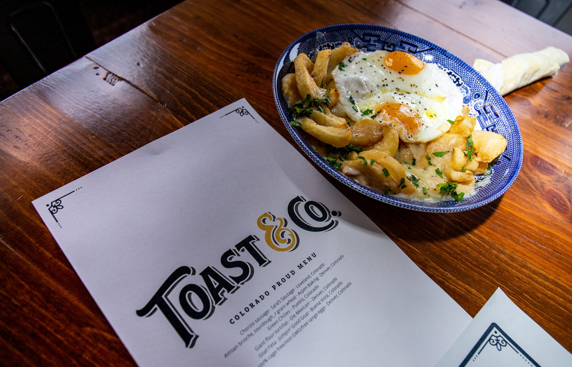 A menu for the restaurant Toast & Co. with a plated menu item featuring french fries and eggs