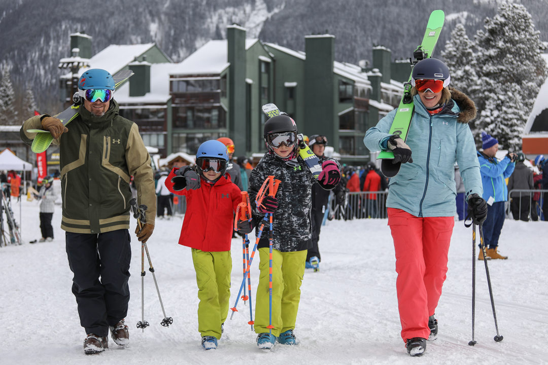 A family of four walks on the snow at Copper Mountain with ski gear in hand.